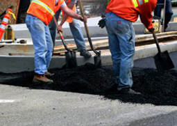 workers repairing asphalt in parking lot